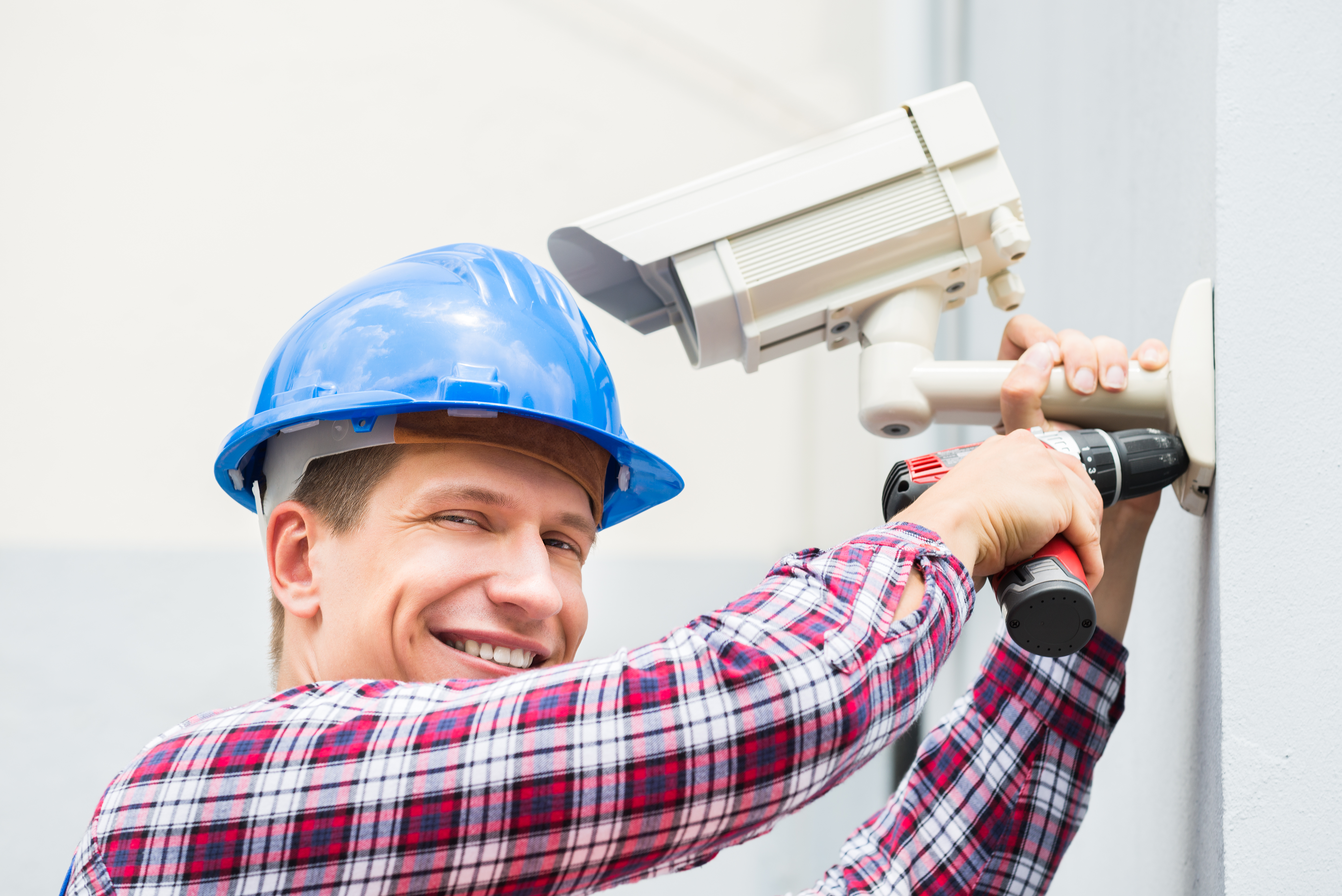 Close-up Of Happy Male Technician Installing Camera On Wall